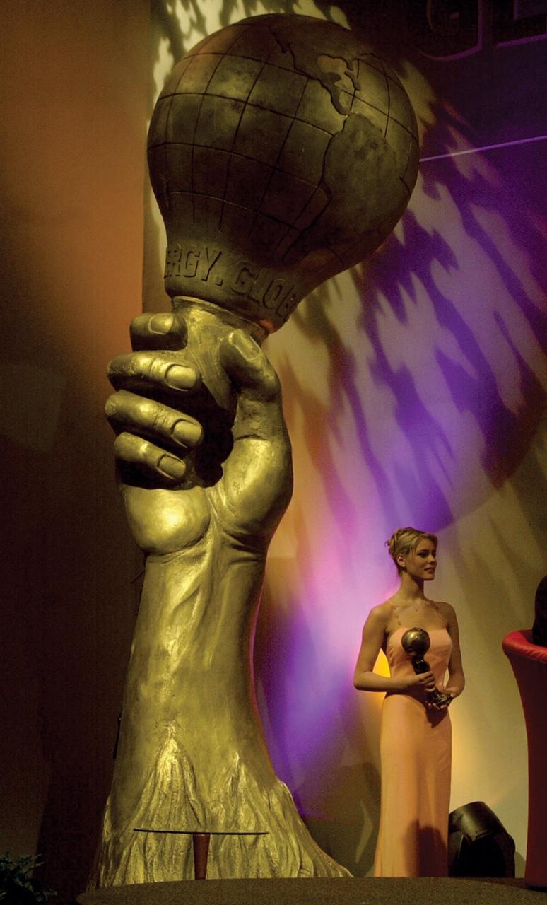 Bild einer Preisverleihung vor einer großen Statue einer Weltkugel.